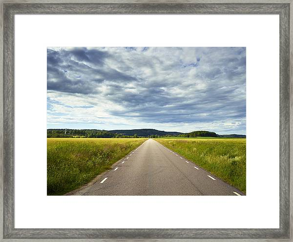 Clouds Above Country Road Framed Print by Johner Images