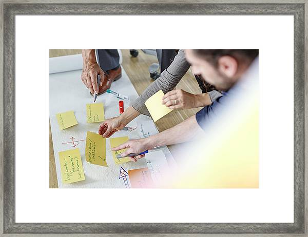 Colleagues Working Together On A Project Framed Print by Westend61