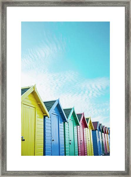 Colourful Beach Huts Along The Seafront Framed Print