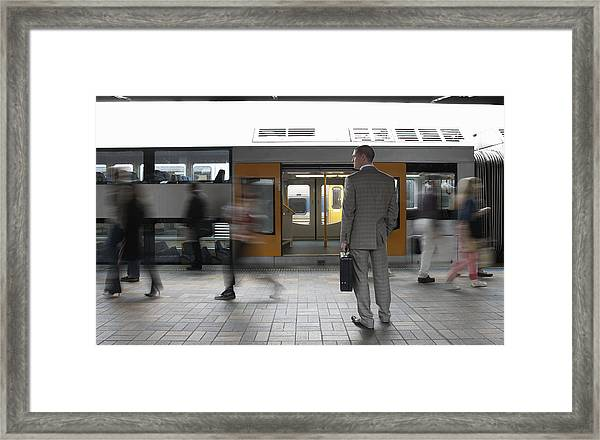 Commuters Passing Businessman On Platform,  (blurred Motion) Framed Print by Toby Burrows