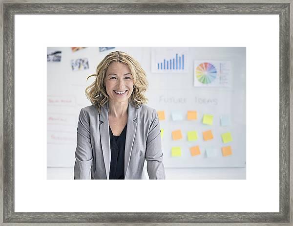 Confident Businesswoman Against Whiteboard Framed Print by Xavierarnau