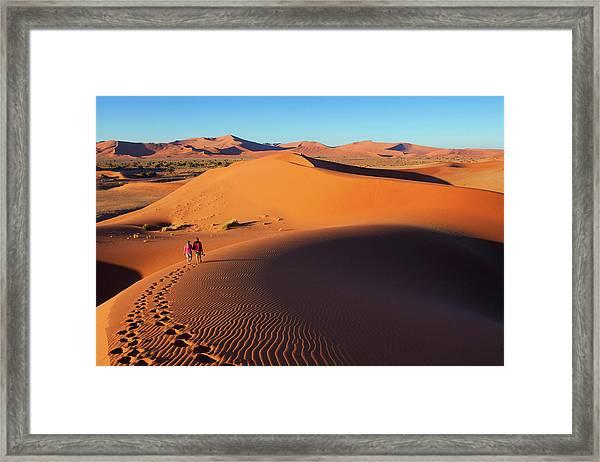 Couple Walking Along Edge Of Sand Framed Print