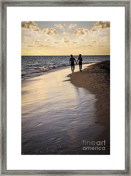 Couple Walking On A Beach Framed Print