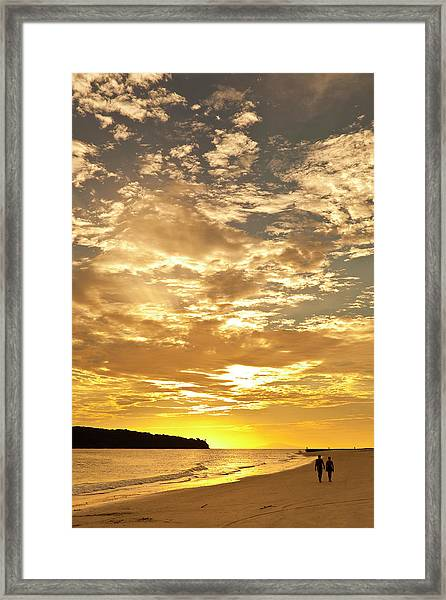 Couple Walking On Beach At Sunset Framed Print