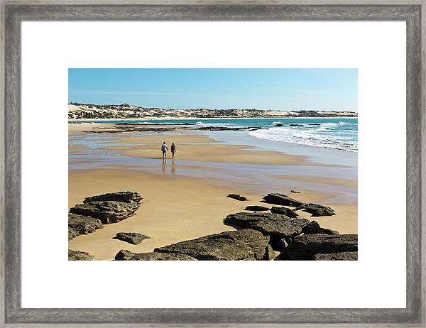Couple Walking On Empty Beach In Framed Print