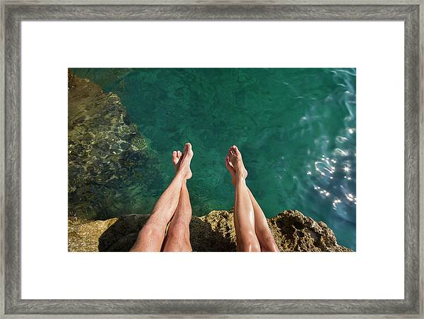 Couples Legs Above Turquoise Ocean Framed Print by Picturegarden
