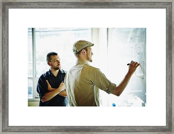 Coworkers Working On Project On Whiteboard Framed Print by Thomas Barwick