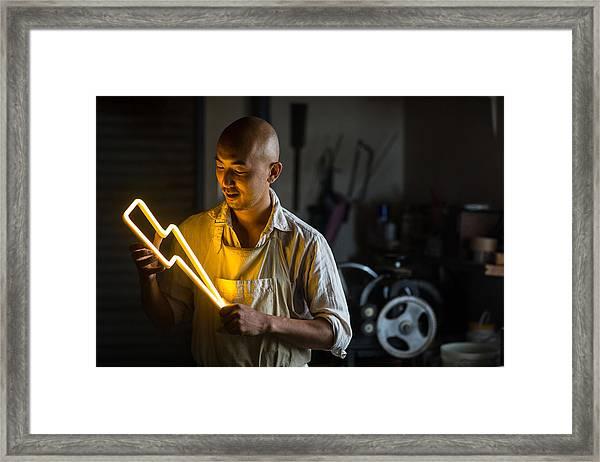 Craftsmen Holding A Lightning Bolt Shaped Neon Light Framed Print by Trevor Williams