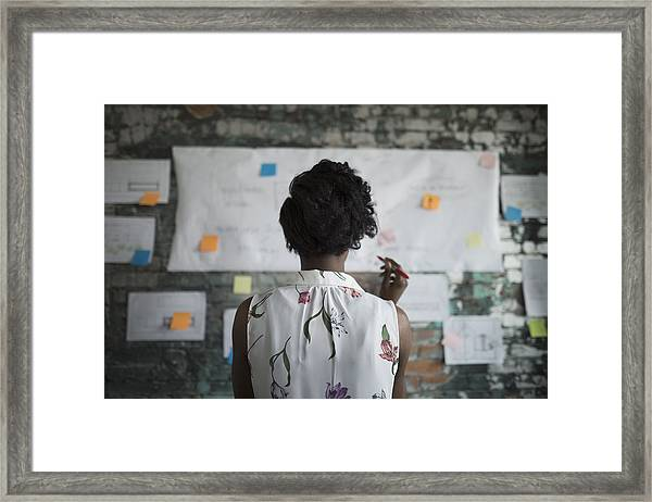 Creative Businesswoman Brainstorming, Reviewing Flow Chart Hanging On Brick Wall In Office Framed Print by Hero Images