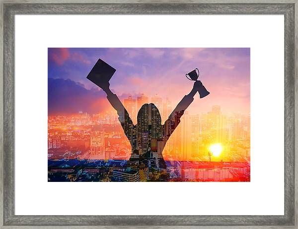 Digital Composite Image Of Woman Holding Award And Cityscape Against Sky During Sunset Framed Print by Jirapatch Iamkate / EyeEm