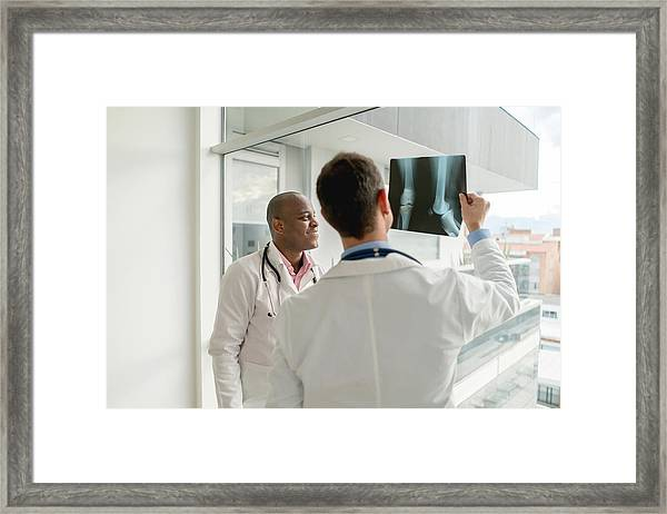 Doctors Looking At An X-ray Framed Print by Andresr