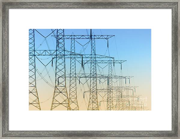 Electricity Pylons Standing In A Row Framed Print