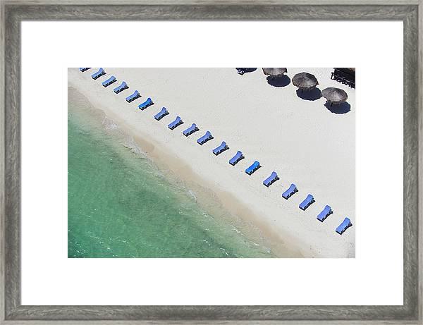 Empty Sun Loungers On A Tropical Beach Framed Print