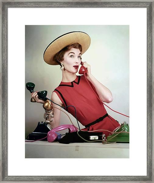 Evelyn Tripp Holding Telephones Framed Print by Erwin Blumenfeld