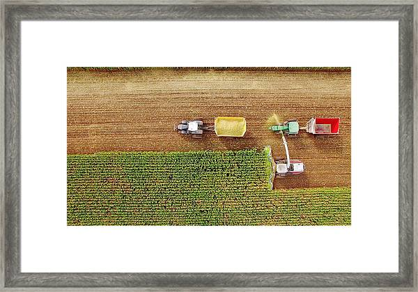 Farm Machines Harvesting Corn In September, Viewed From Above Framed Print by JamesBrey