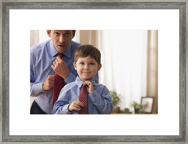 Father And Son Fixing Ties Together Framed Print by SelectStock