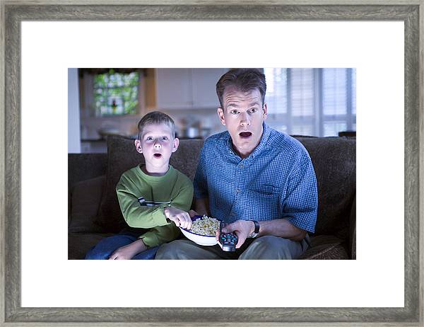 Father And Son With Remote Control And Popcorn Framed Print by Thinkstock Images