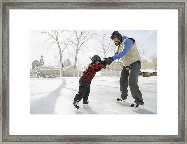 Father Teaching Son To Ice-skate On Outdoor Rink Framed Print by Hero Images