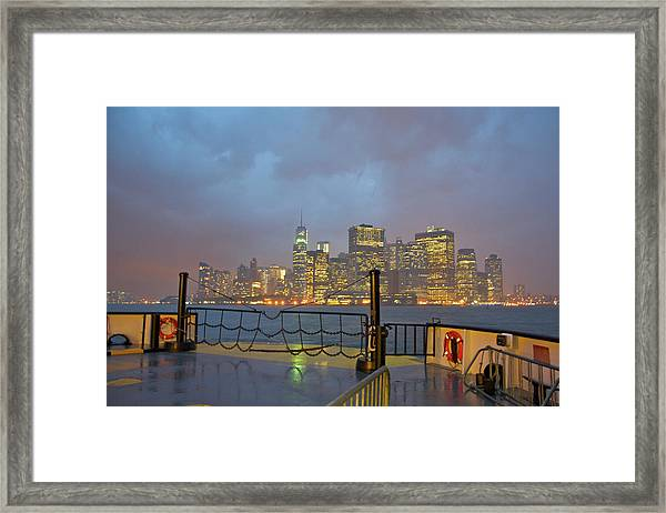 Ferry Moving Towards Lit Skyscrapers At Framed Print