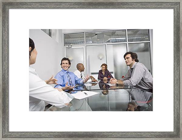 Five Businesspeople Sitting At Conference Table, Discussing Framed Print by Bob Handelman