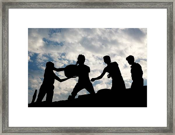 Four Men Manouevering Cement Basket Framed Print by Adrian Pope