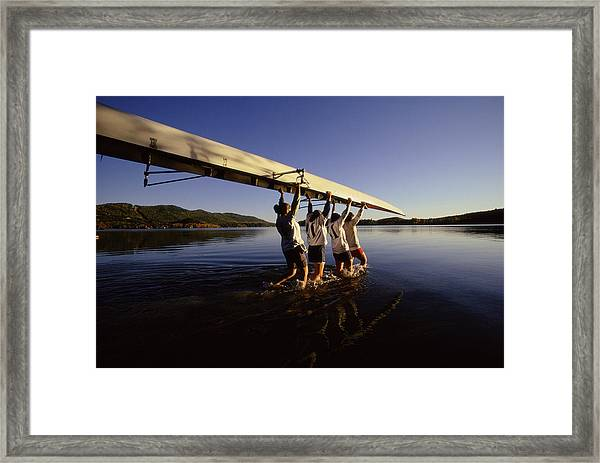 Four Young Women Carrying Canoe Into Lake Framed Print by Bob Handelman