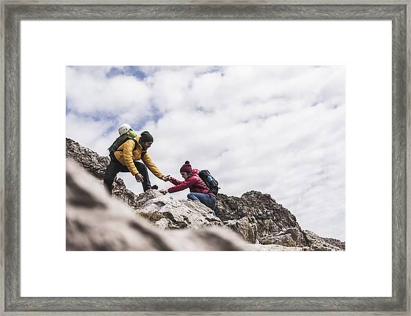 Germany, Bavaria, Oberstdorf, Man Helping Woman Climbing Up Rock Framed Print by Westend61