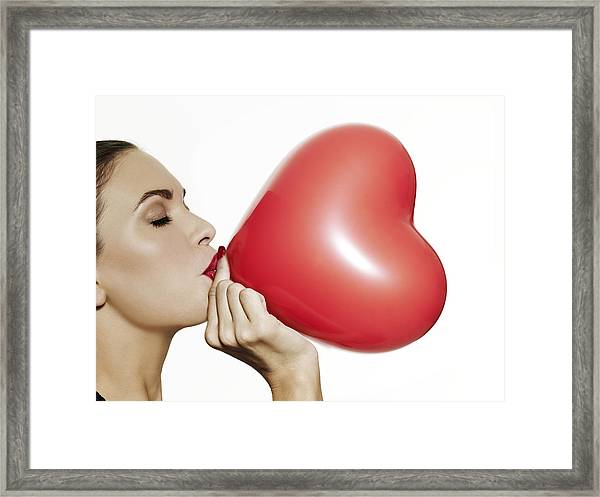 Girl Blowing Up A Red Heart Shaped Balloon Framed Print by Elizabeth Hachem