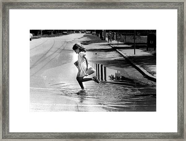 Girl Playing In A Puddle Framed Print by Retro Images Archive