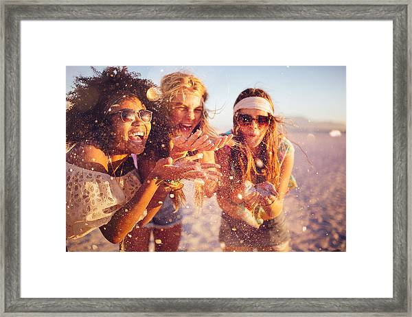 Girls Blowing Confetti From Their Hands On A Beach Framed Print by Wundervisuals