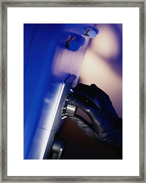 Gloved Hand Opening A Safe Framed Print by Photodisc