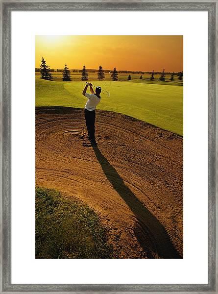 Golfer Taking A Swing From A Golf Bunker Framed Print