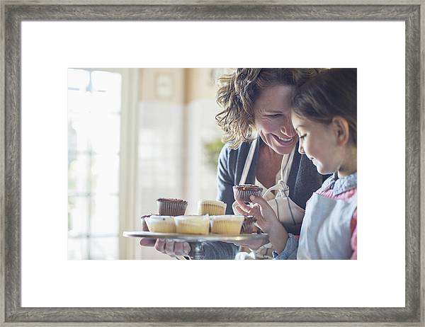 Grandmother Offering Granddaughter Cupcakes Framed Print by Caiaimage/Sam Edwards