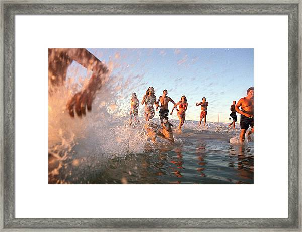 Group Of Young Adults Running Through Water At Ocean's Shore Framed Print by Sean Murphy