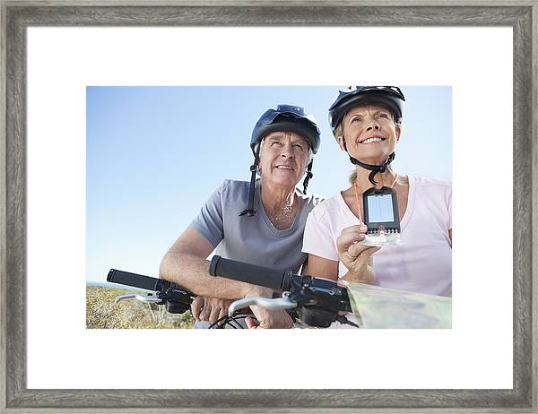 Happy Mature Woman Mountain Biking With Man Using Gps Framed Print by OJO Images