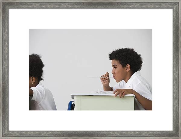 Hispanic Boy Blowing Spitball On Girl In Class Framed Print by Jose Luis Pelaez Inc