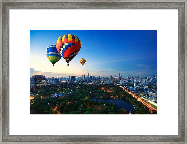 Hot Air Balloons Fly Over Cityscape At Sunset Background Framed Print by Busakorn Pongparnit