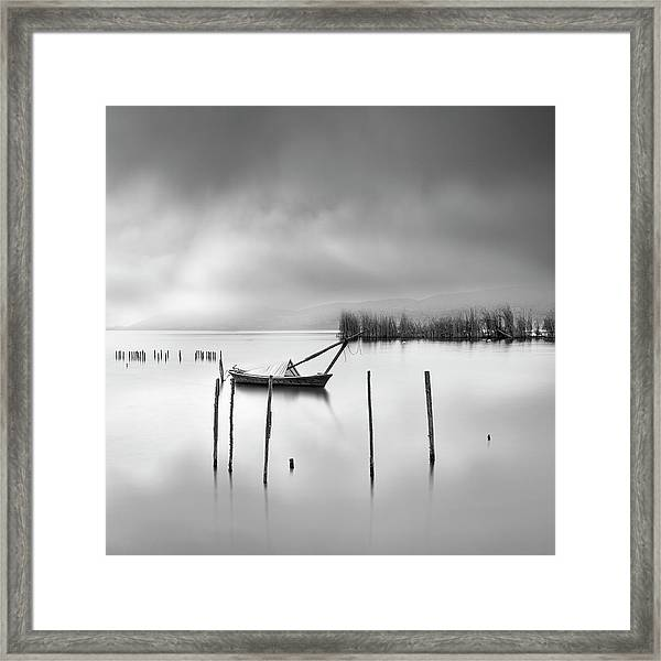 Lake View With Poles And Boat Framed Print