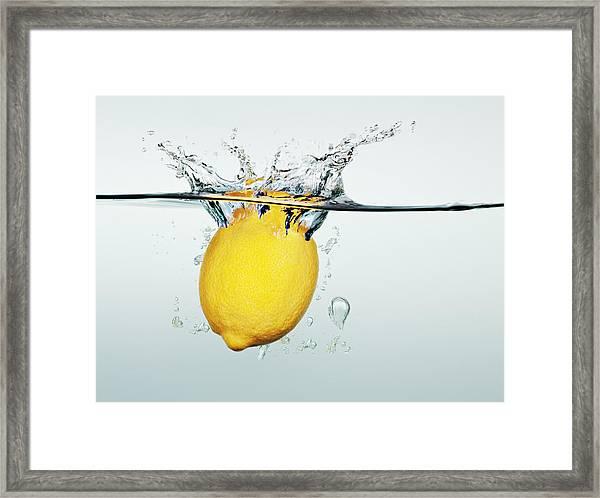 Lemon Splashing In Water Framed Print by Martin Barraud
