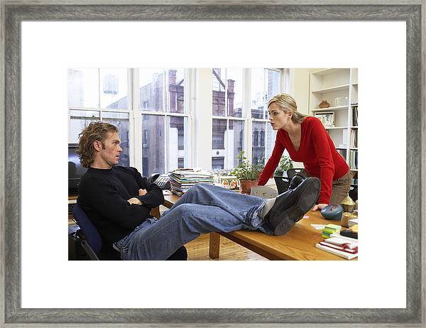 Male Office Worker With Feet On Desk, Woman Leaning On Edge Of Desk Framed Print by Christopher Robbins