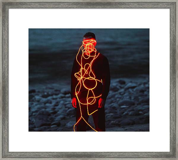 Man Entangled With Neon Wires Against Nature Background Framed Print by Vasilina Popova