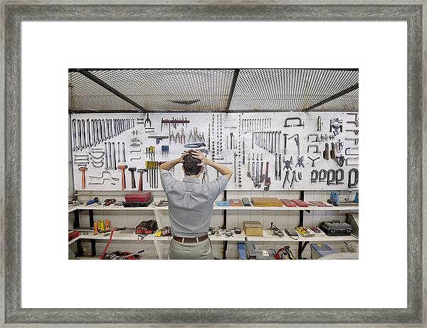 Man Holding Head By Wall Of Tools Framed Print by Lester Lefkowitz