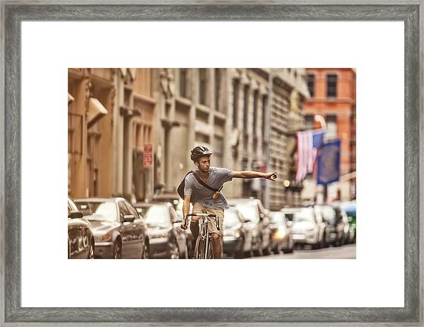 Man Riding Bicycle On City Street Framed Print by Sam Edwards