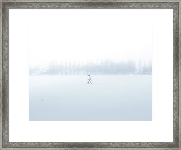 Man Walking Through A Snowfield Framed Print by Taketan