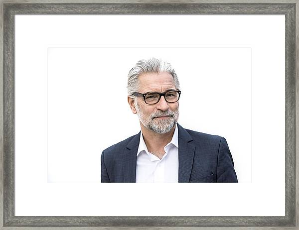 Mature Grey-haired Man In Suit Smiling Framed Print by Robin Skjoldborg
