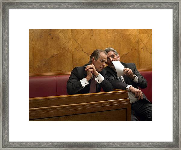 Mature Man Whispering To Colleague In Pew Framed Print by Michael Blann