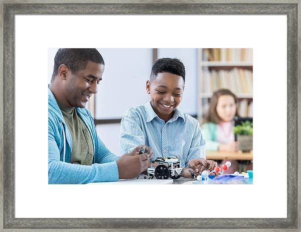 Mentor And Male Student Working Together On A Robot Framed Print by Steve Debenport