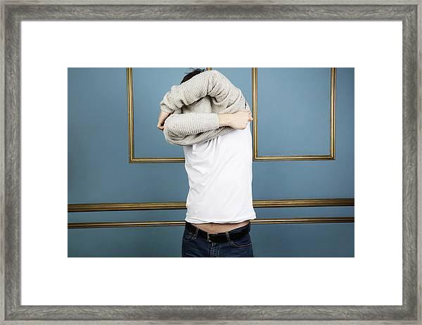 Mid Adult Man Taking Off Jumper Framed Print by Imperia Staffieri