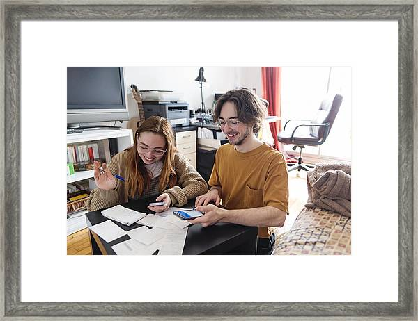 Millennial Couple Using Digital Payment To Share Expense. Framed Print by Martinedoucet