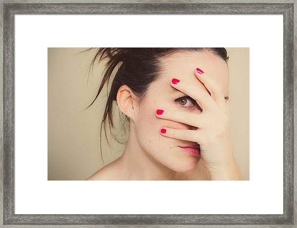 Misterious Girl With Red Nails And Hand On Face. Framed Print by Volanthevist